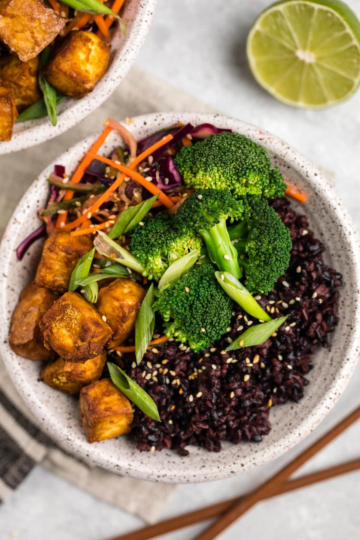 close up photo of black rice bowl with wooden chopsticks