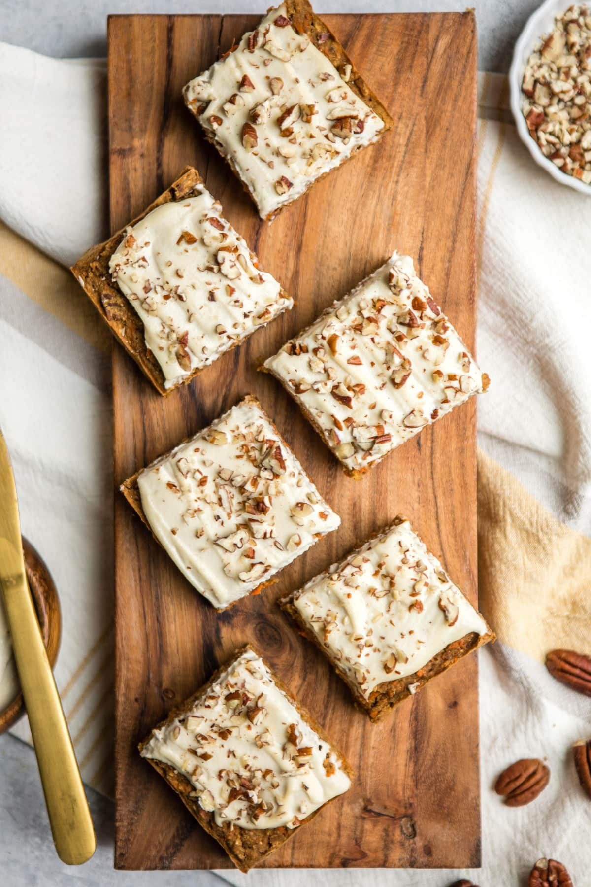 squares of frosted vegan carrot cake on wood serving plank
