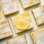close up shot of lemon bars topped with powdered sugar and lemon slices on white background