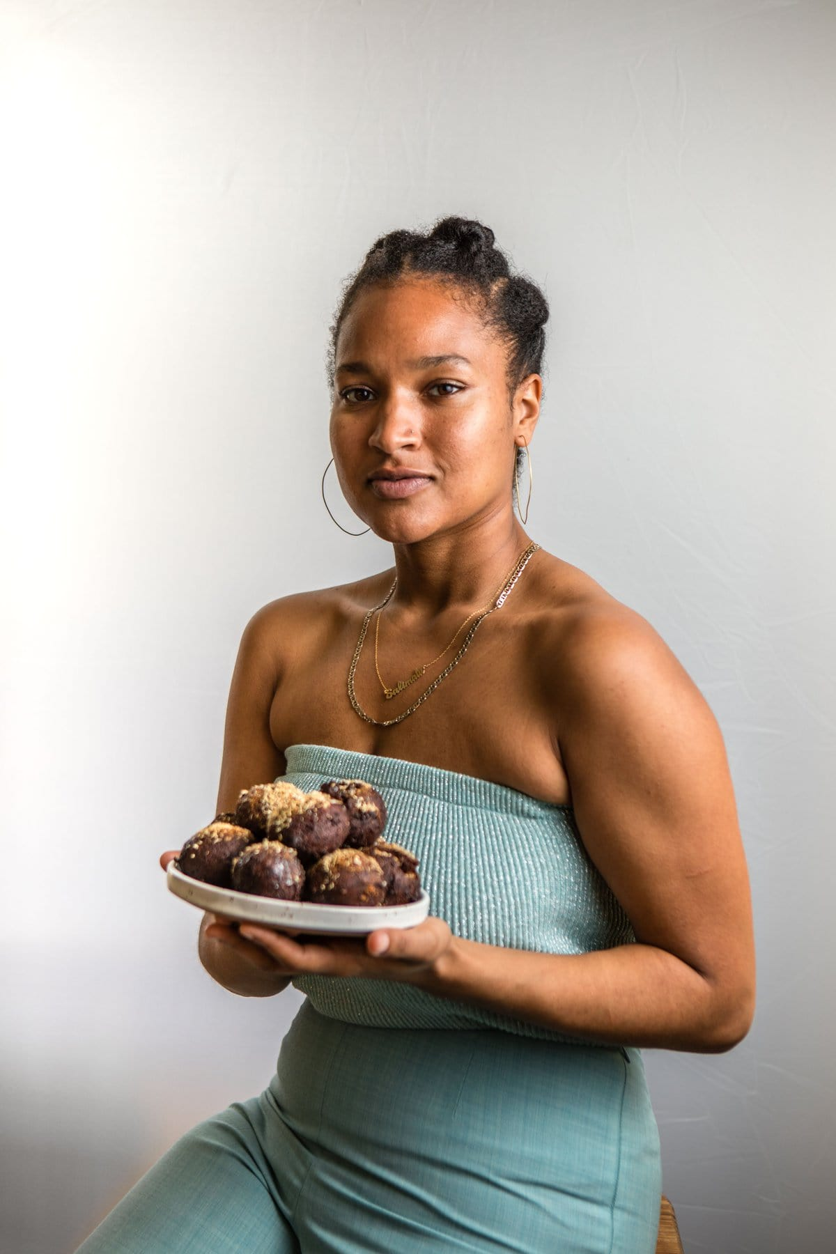 chef salimatu holding white plate of chocolate puff puff