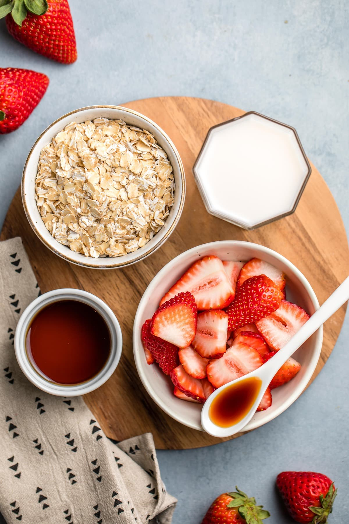 ingredients for strawberries and cream oatmeal arranged on round wood cutting board