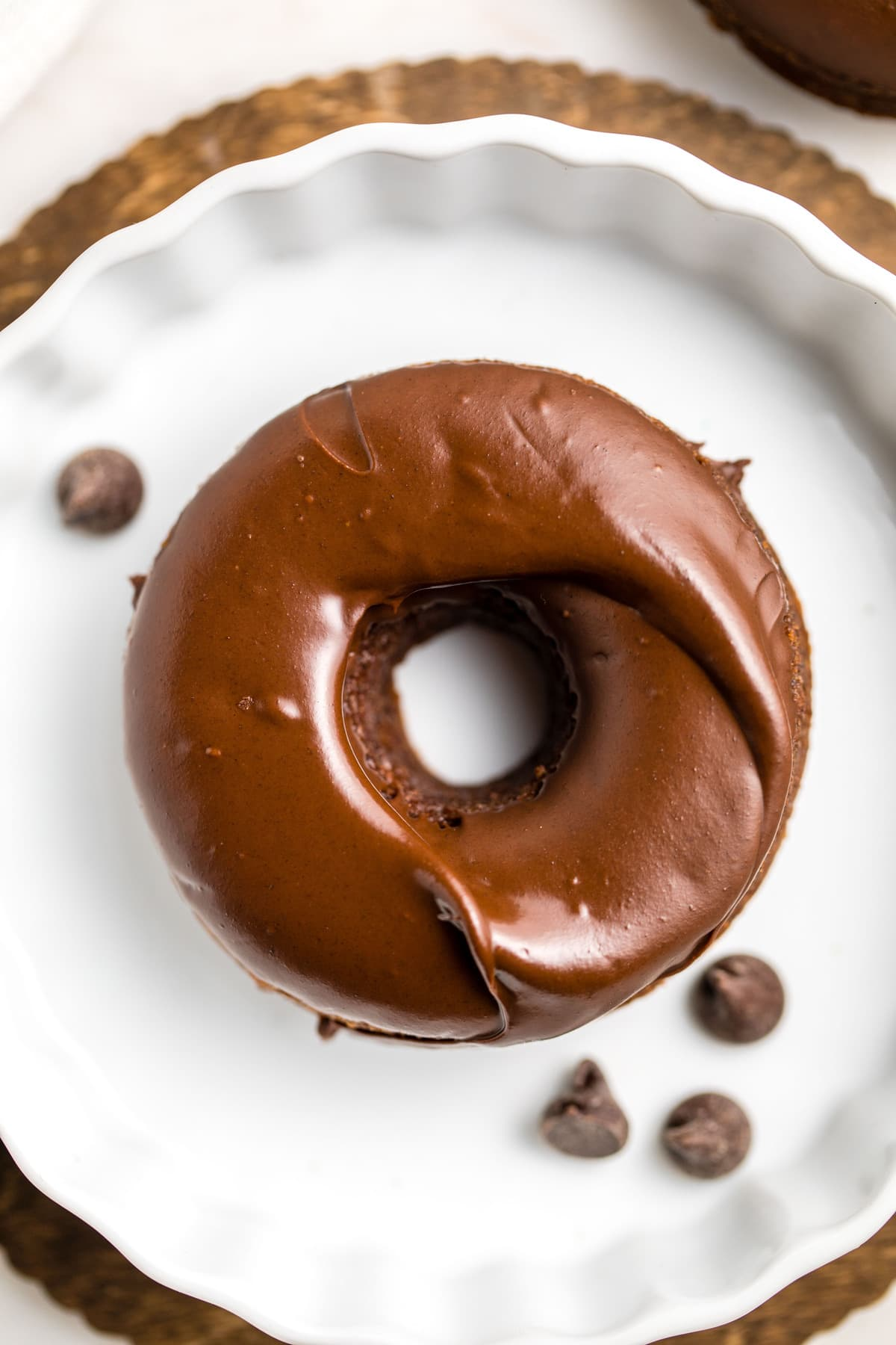 close up photo of chocolate covered donut on white plate with chocolate chips
