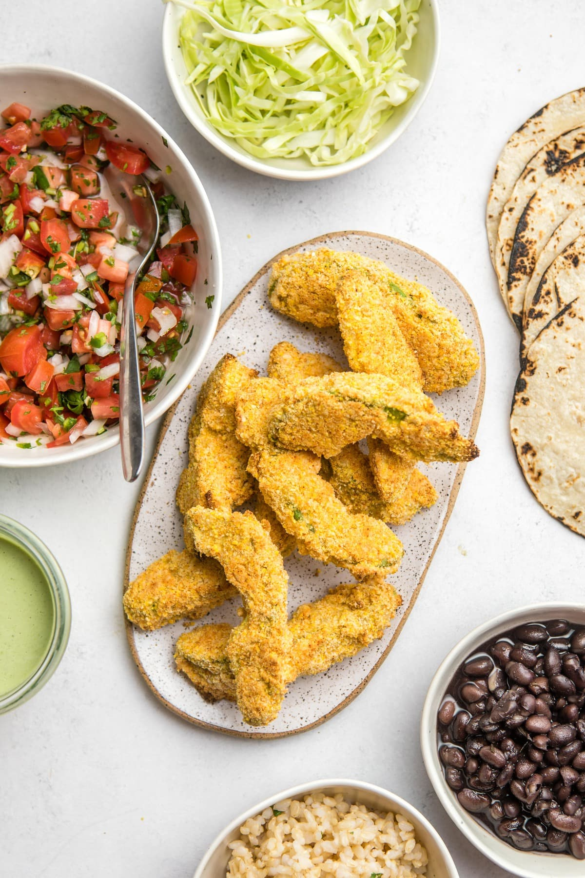 crispy baked avocado fries on oval plate on white background