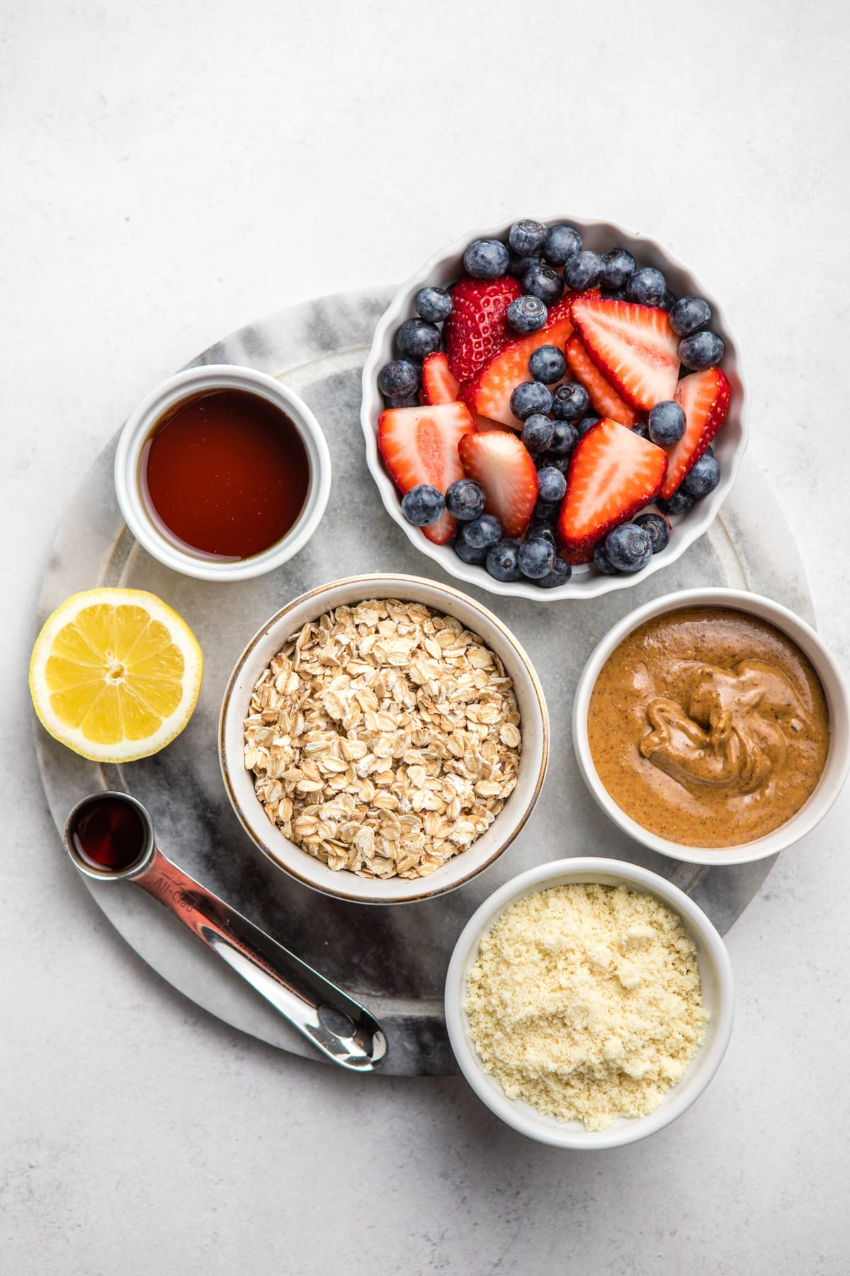 ingredients for berry crumble on round marble cutting board