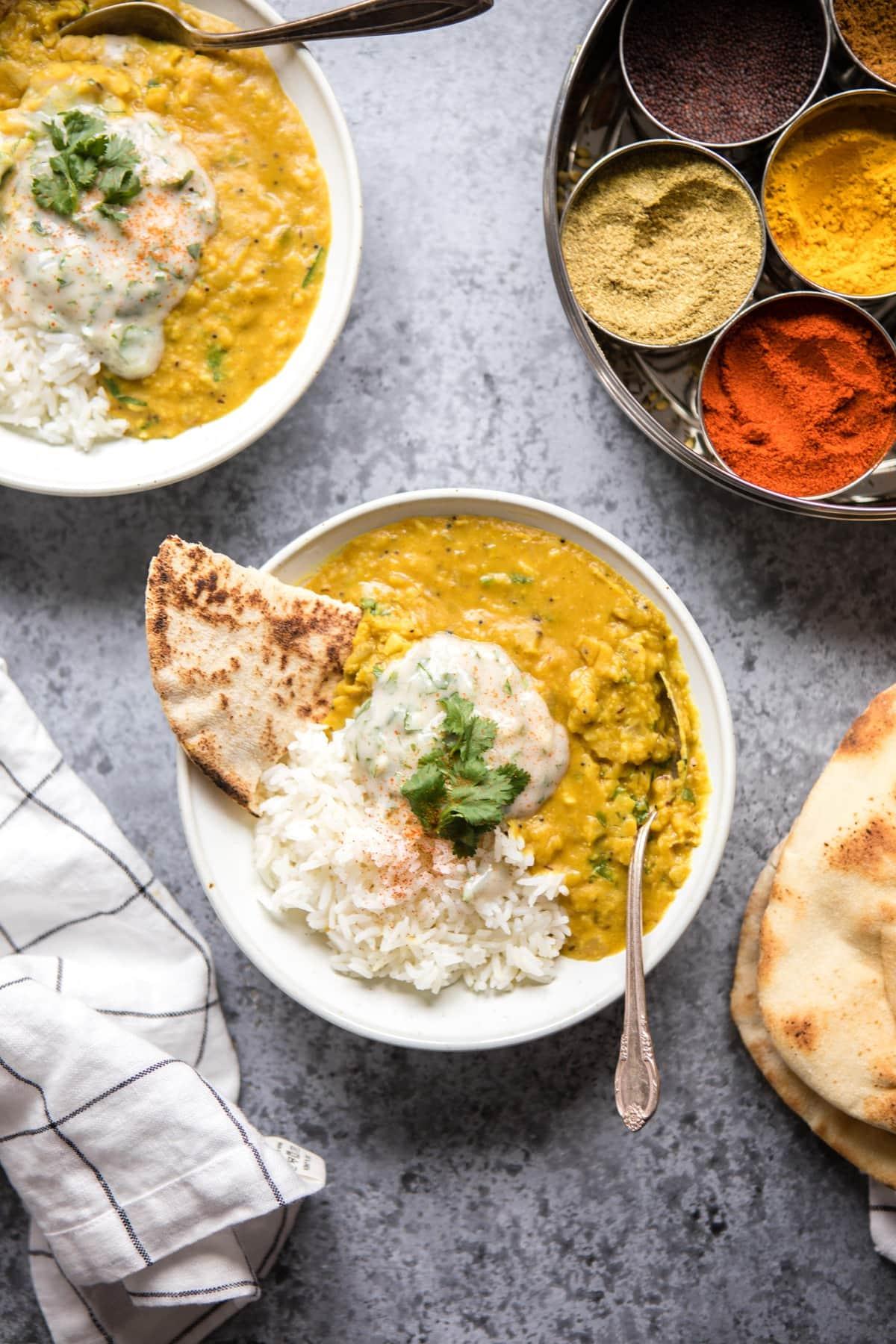 two bowls of dal tadka with rice and raita