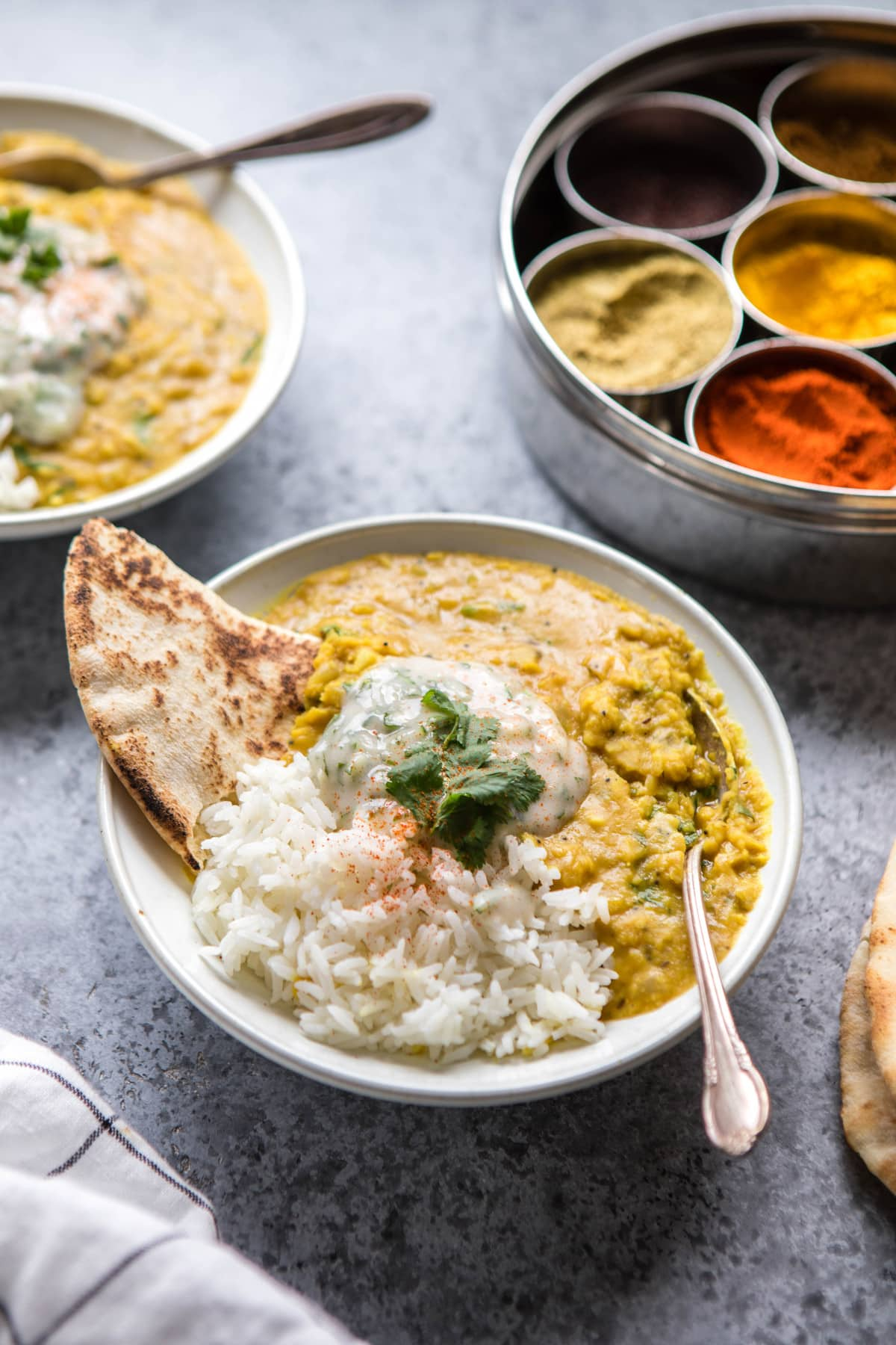 instant pot dal with rice, naan, and raita in white bowl
