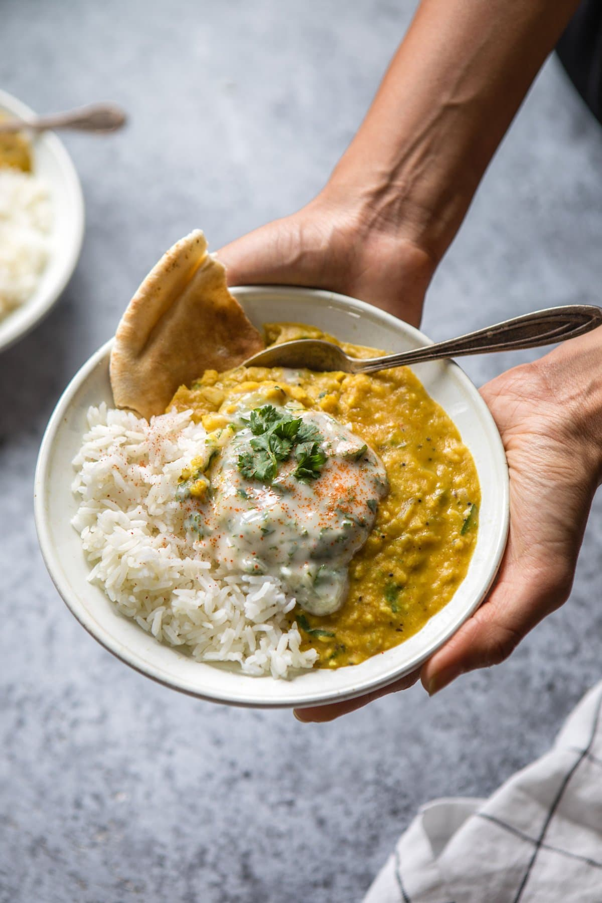 two hands holding bowl of dal tadka with rice, naan, and raita