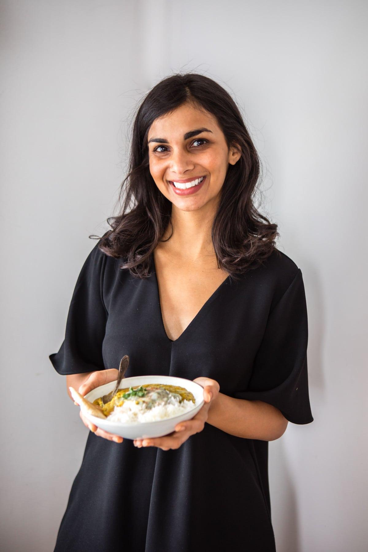 Nisha smiling while holding bowl of Dal Tadka