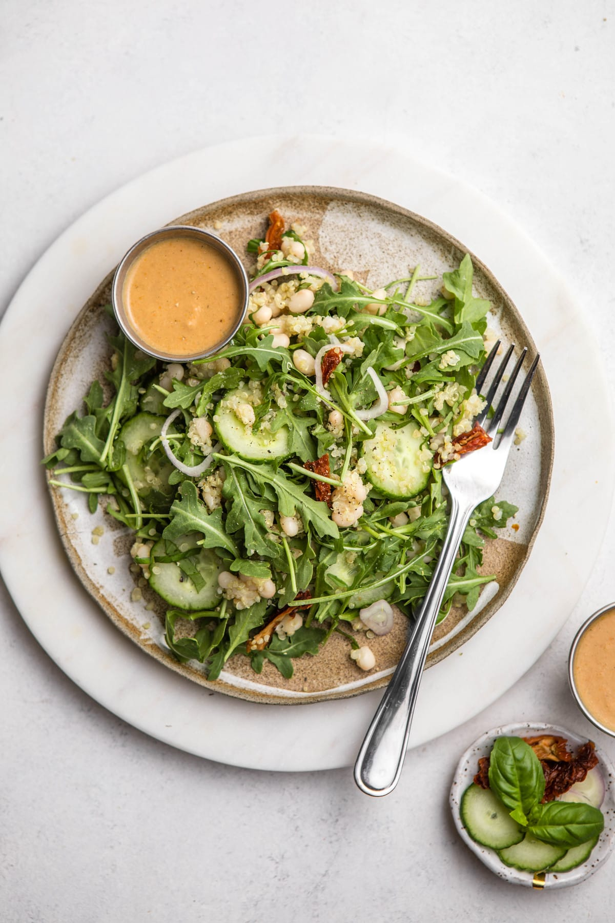 quinoa and arugula salad on tan ceramic plate with dressing on the side on white background