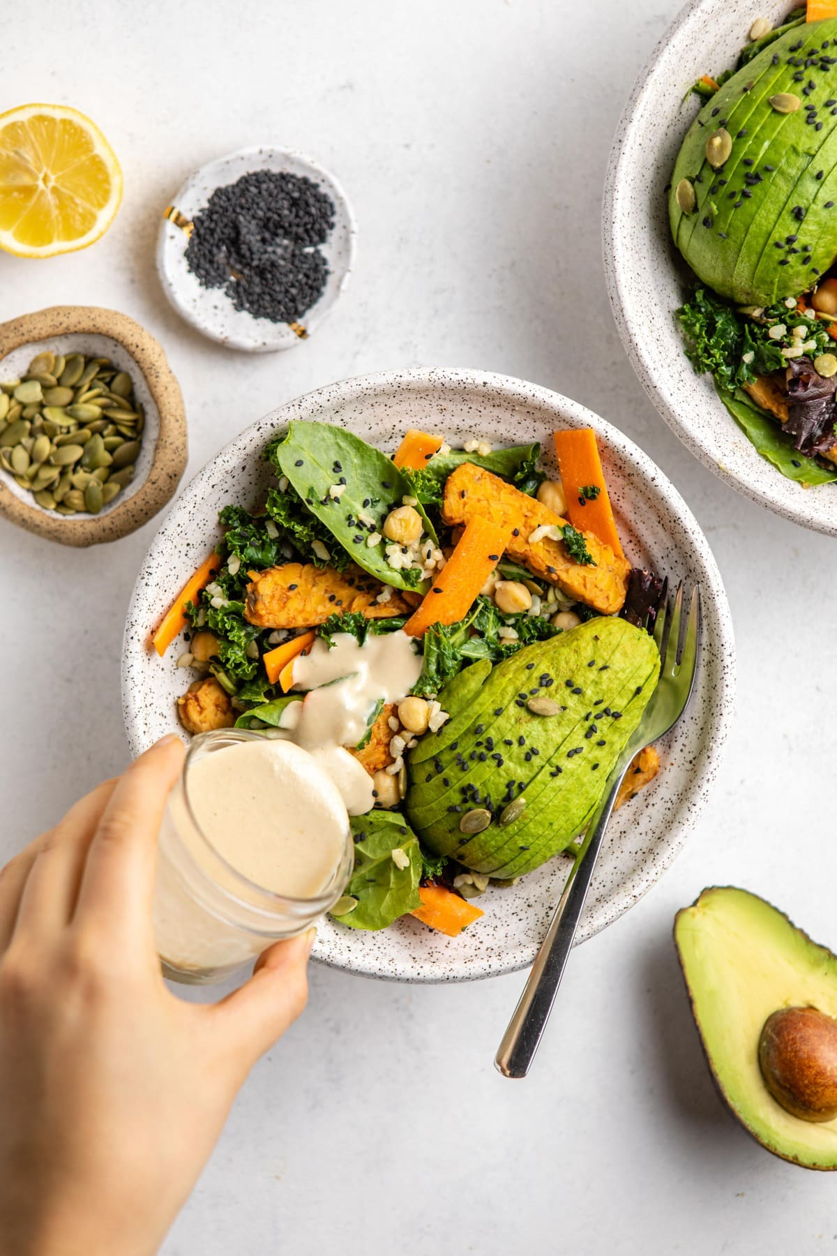 hand pouring creamy miso dress into harvest salad with avocado on the side