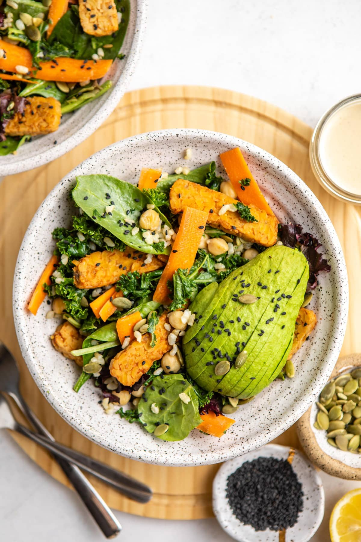 two bowls of simple harvest salad on wood cutting board