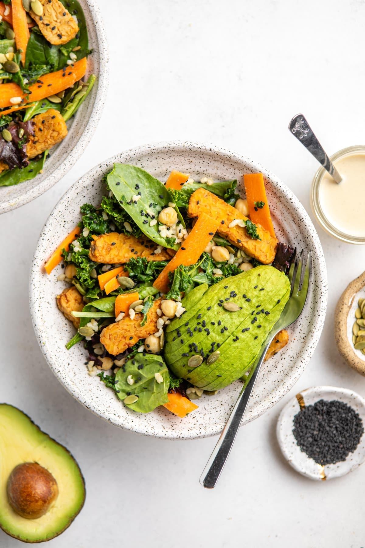 harvest salad in white speckled bowl on white background