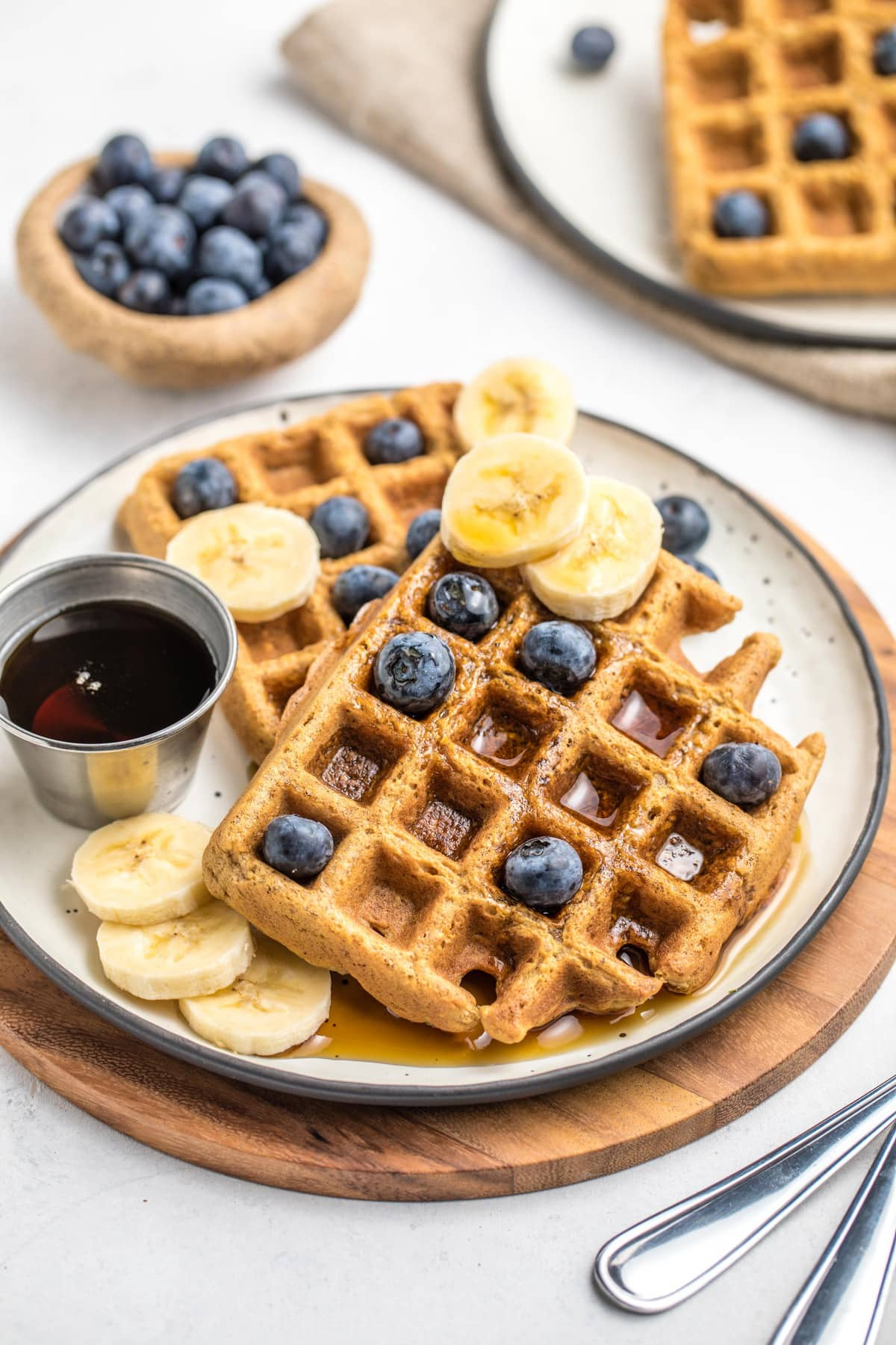 two vegan blender waffles with maple syrup drizzle, blueberries, and banana pieces
