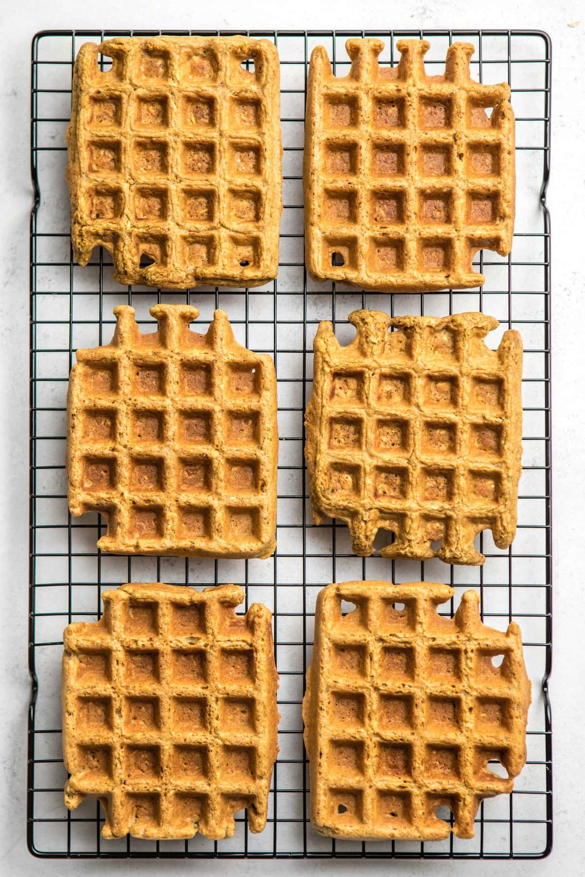 six vegan blender waffles on black cooling rack