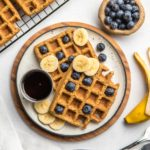 vegan blender waffles on small white plate with blueberries, banana, and maple syrup