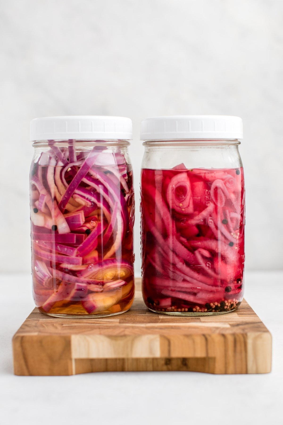 jar of fresh pickled red onions next to jar of week-old pickled red onions