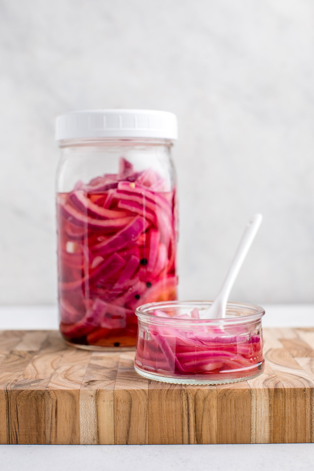 large mason jar and small glass dish of pickled red onions on wood cutting board