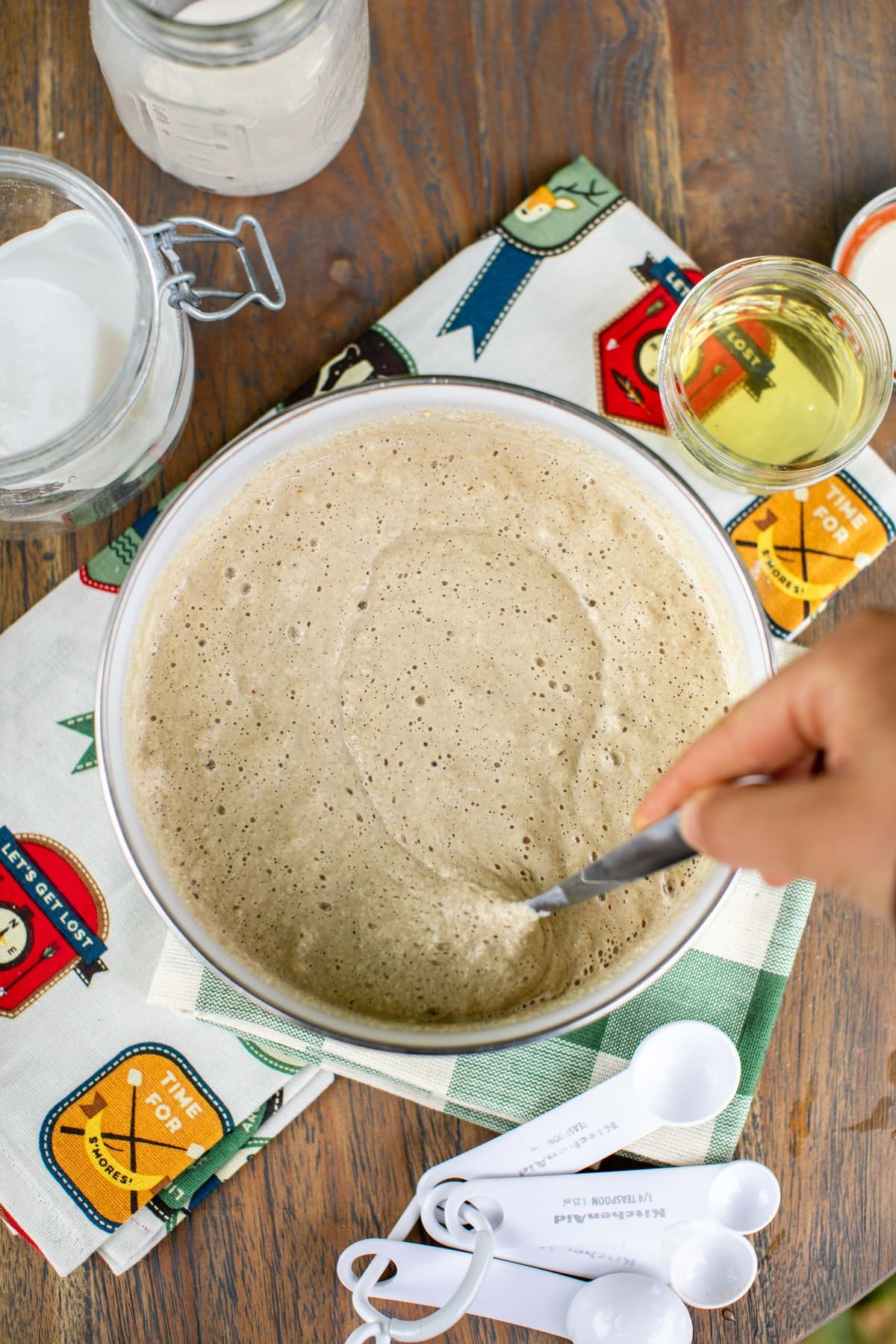 hand mixing bowl of pancake batter on wooden picnic table