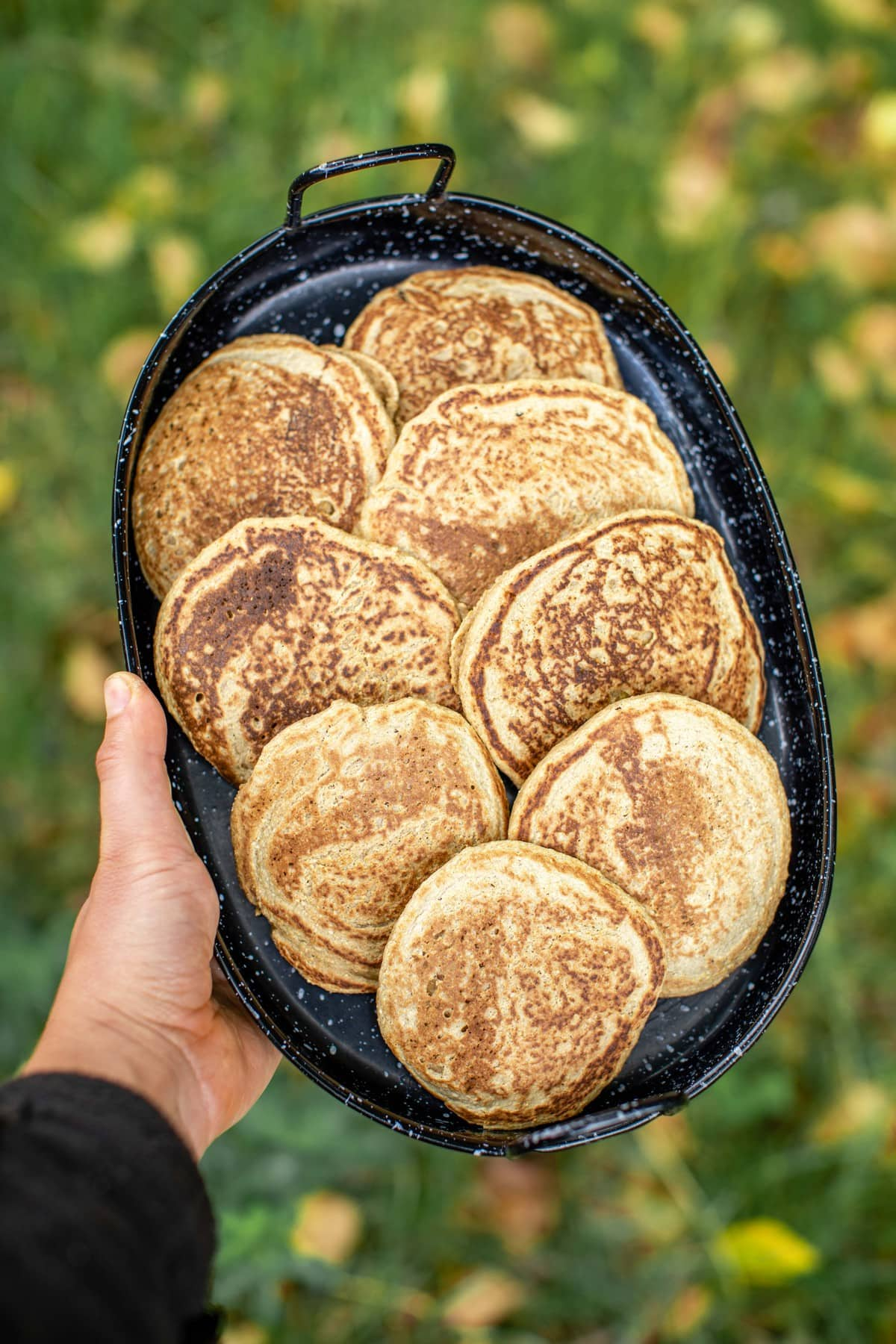 hand holding black aluminum tray of cooked vegan pancakes in grassy field
