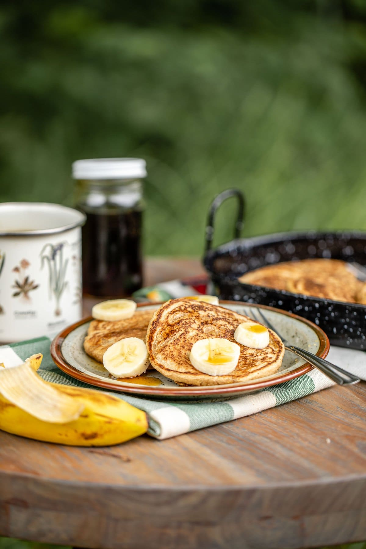 vegan pancakes topped with banana and maple syrup with mug of coffee on picnic table