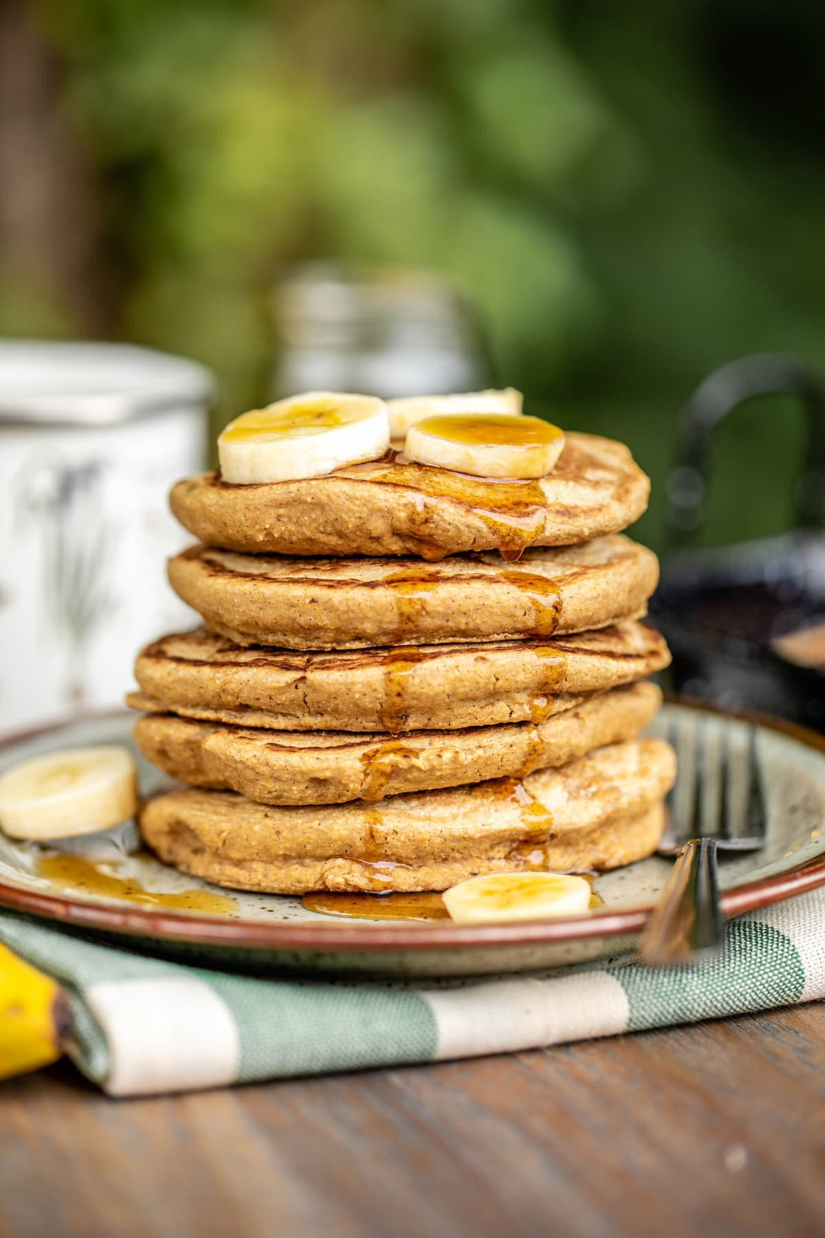 stack of vegan pancakes topped with maple syrup and banana coins on tan speckled plate