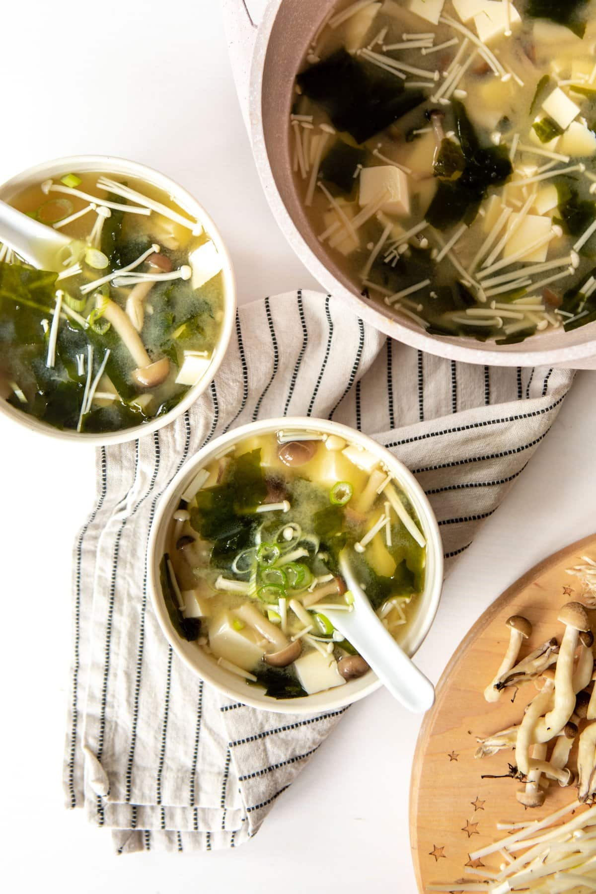 large pot of miso soup with two white small bowls