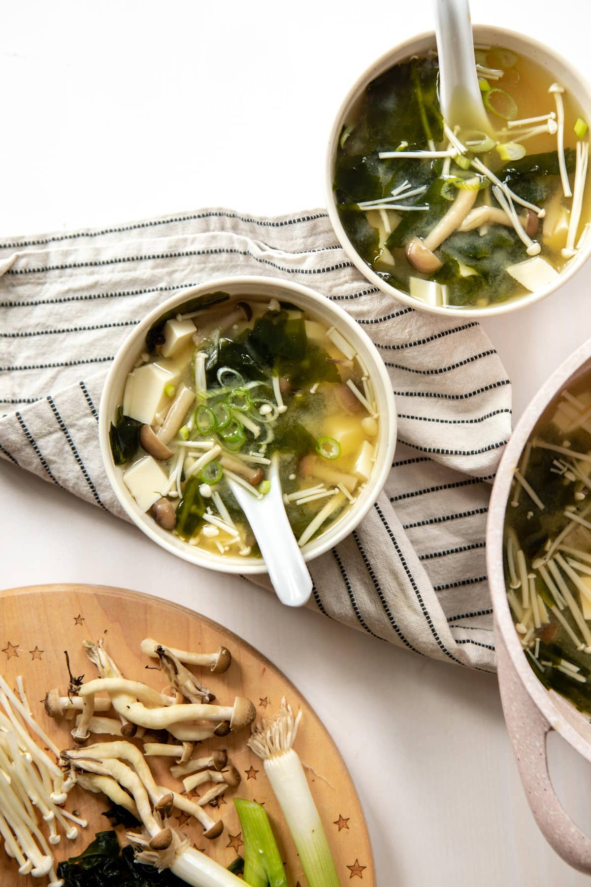 two bowls of miso soup with cutting board of mushrooms