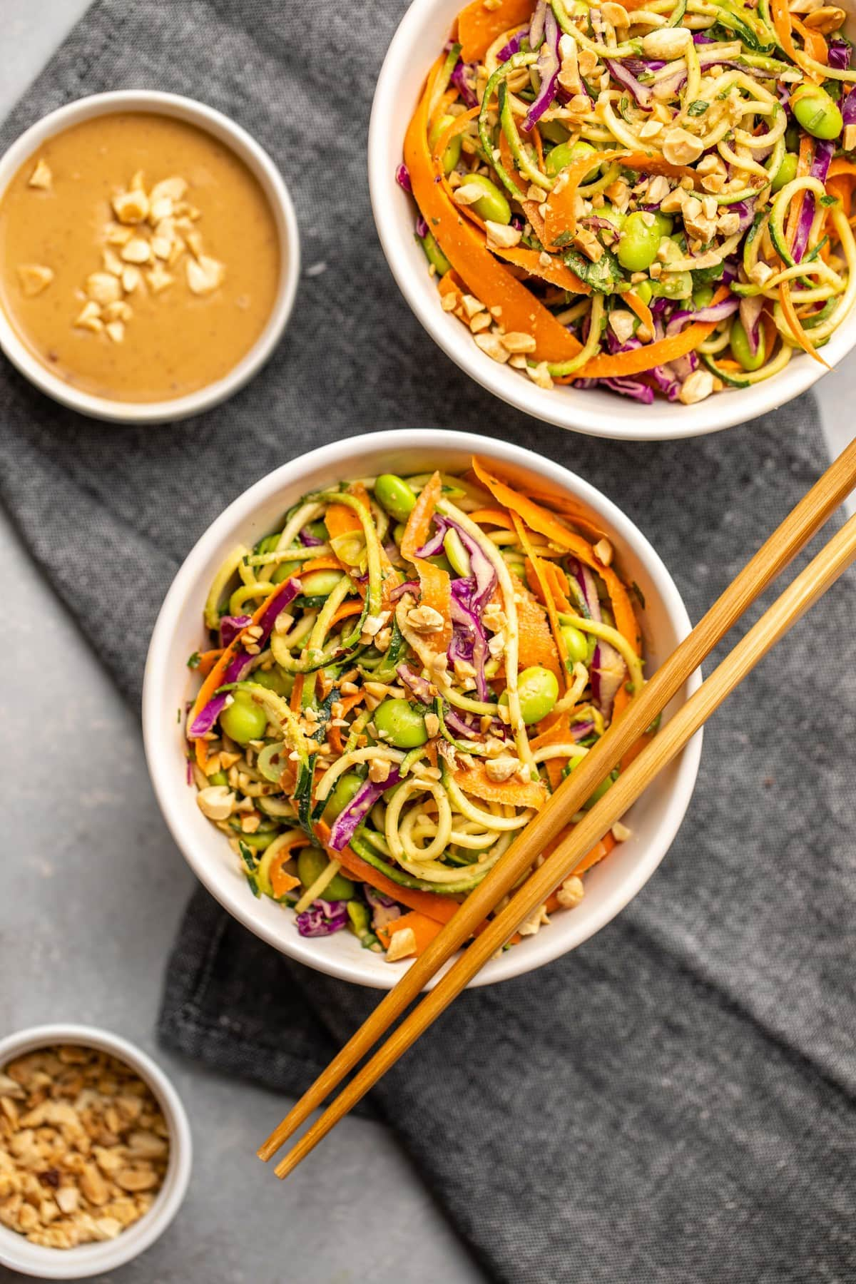 two white bowls of zucchini noodle salad with peanut sauce and wooden chopsticks