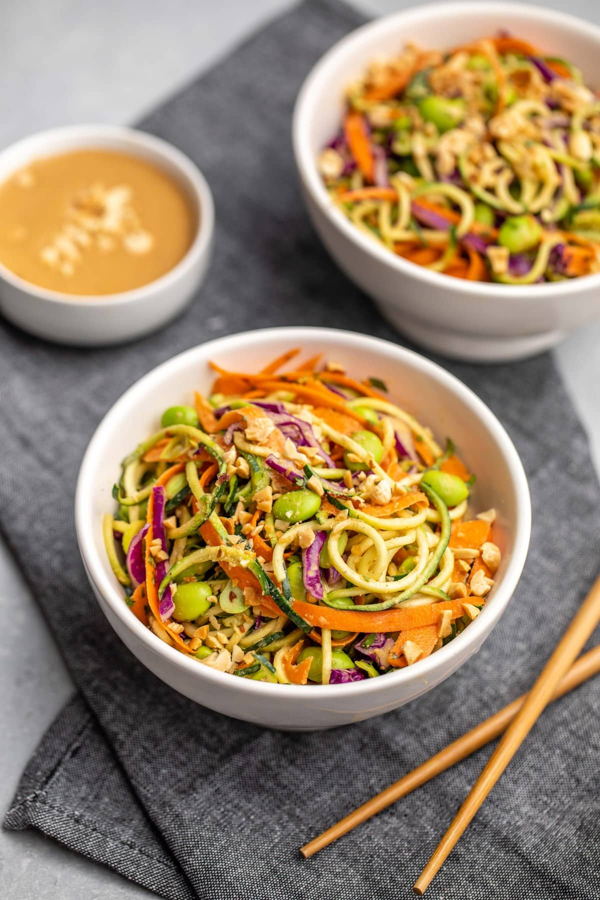 angled shot of two white bowls of zucchini noodle salad with peanut sauce and wooden chopsticks