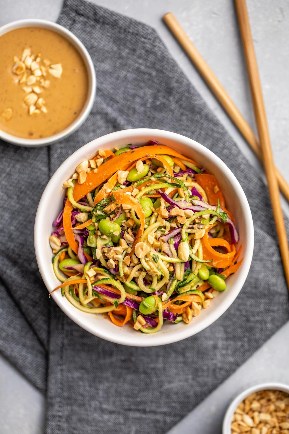 single bowl of zucchini noodle salad with bowls of peanut sauce and chopped peanuts