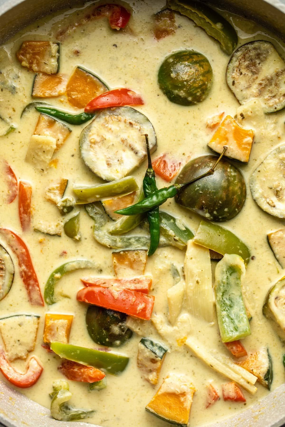 close up photo of cooked thai green curry in grey pot with two thai green chilis on top