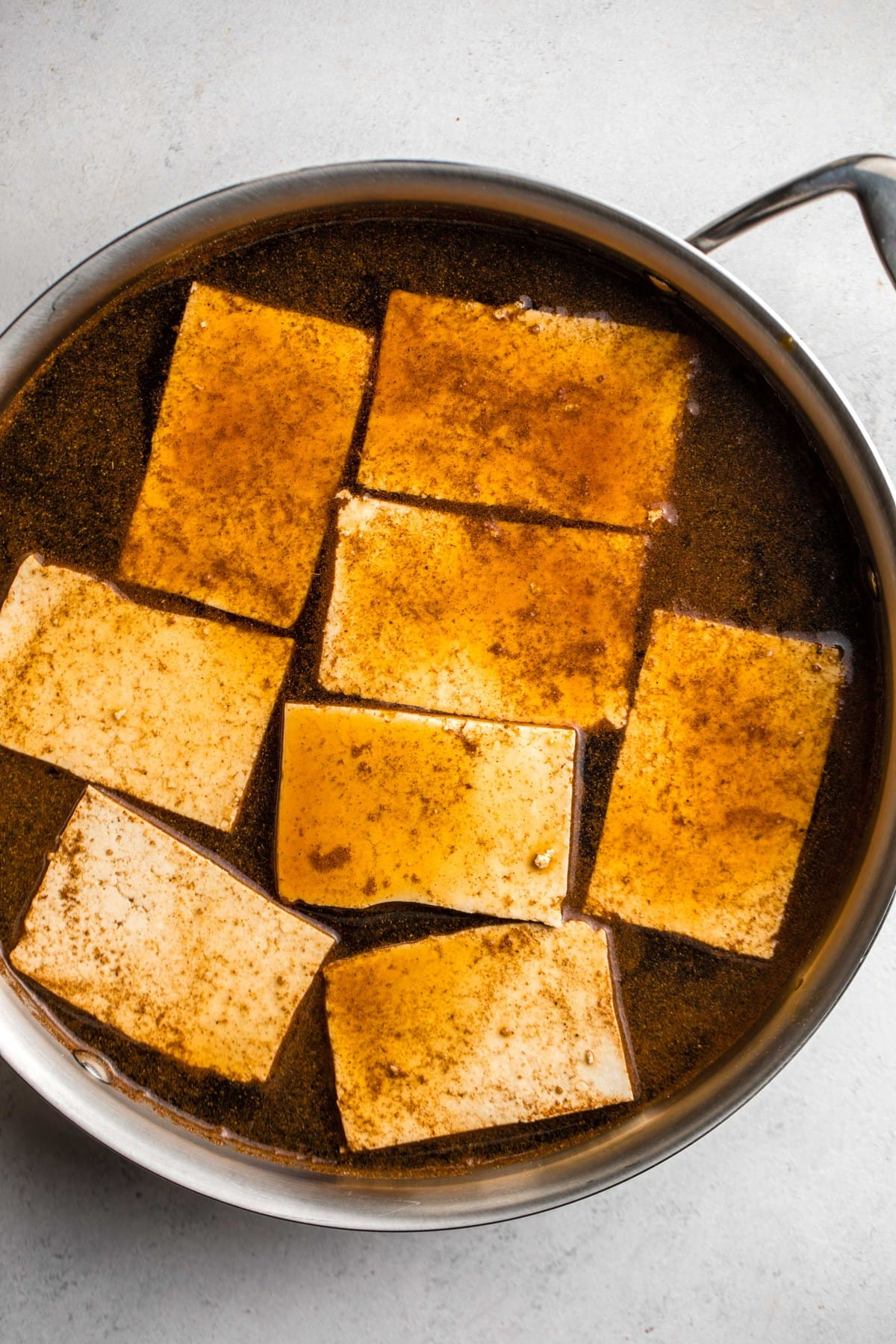 tofu in large grey pot covered in marinade