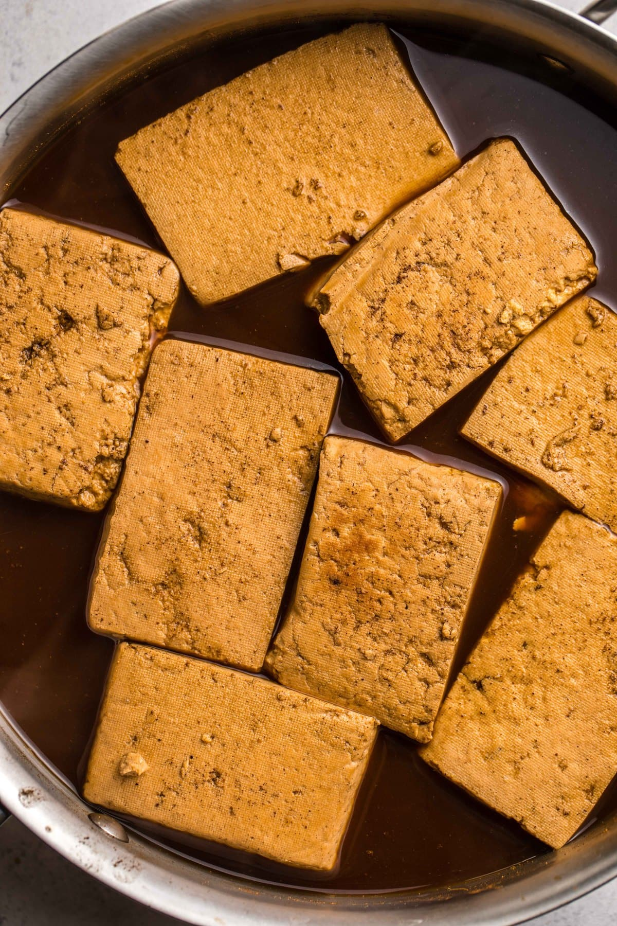 darkened braised tofu after simmering in large metal pot