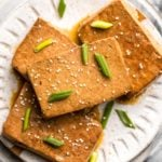 braised tofu on white plate topped with green onion and sesame seeds