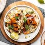 bbq tempeh tacos with lime wedge on white plate with navy napkin