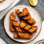 grilled bbq tempeh on white plate with napkin