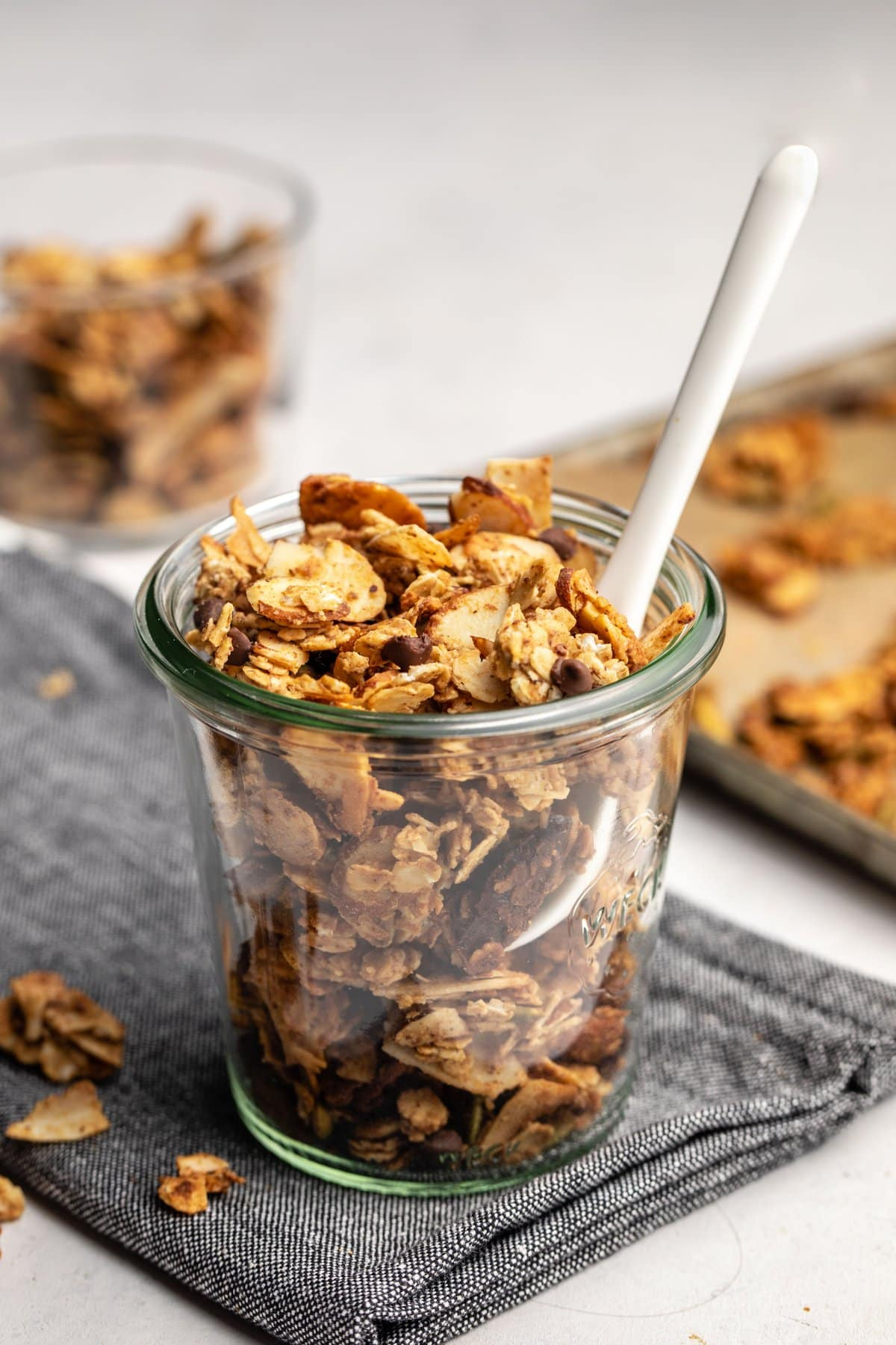 jar of small batch granola with baking tray in the background