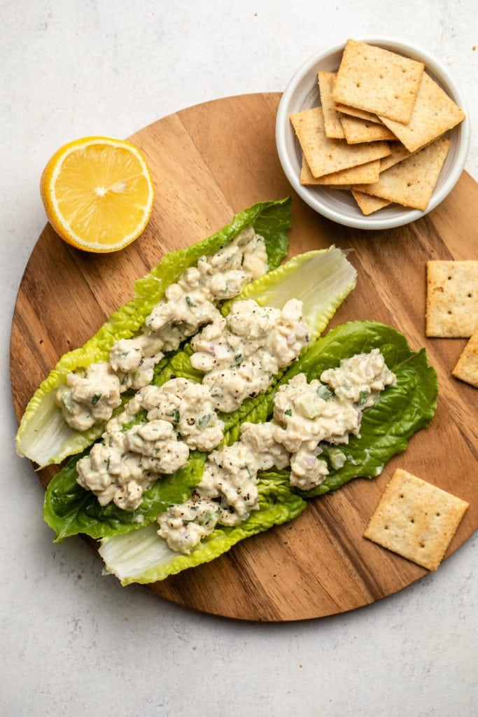 tempeh tuna salad in lettuce boats with crackers and lemon wedge on the side