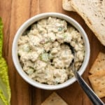 tempeh tuna salad in small white bowl on wood serving board