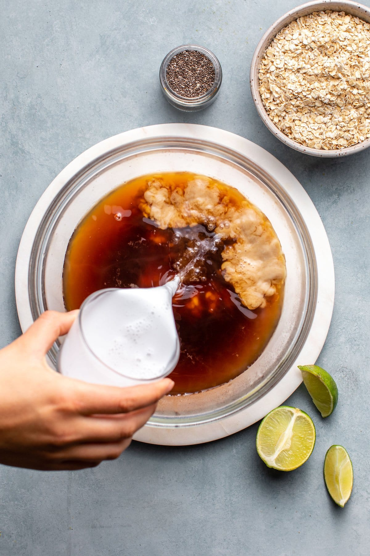 hand pouring coconut milk into large bowl of black tea