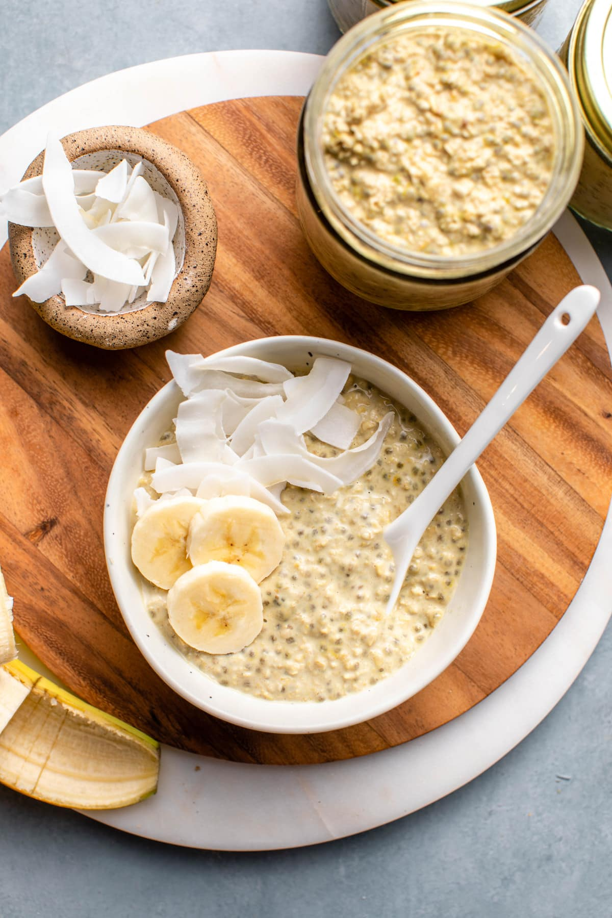 small white bowl of thai tea overnight oats topped with coconut and banana on round wood cutting board