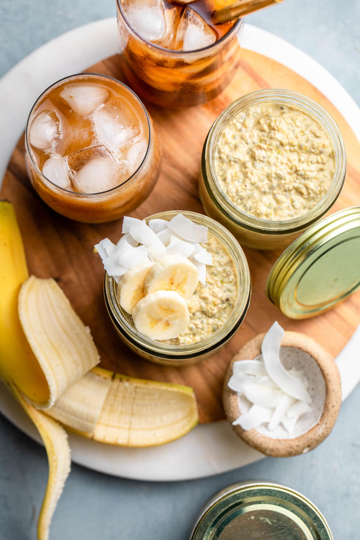 thai tea overnight oats in glass jars topped with banana and coconut