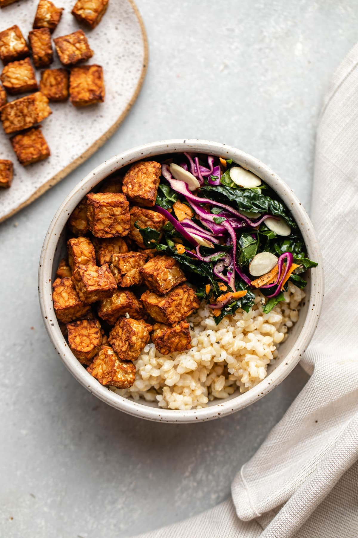 crispy tempeh, kale salad, and rice in bowl