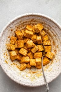 seasoned tempeh in white speckled bowl with spoon