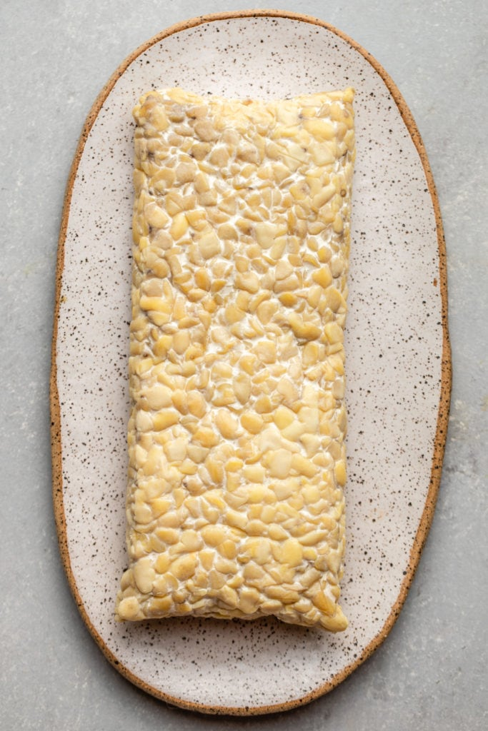block of uncut tempeh on white serving board