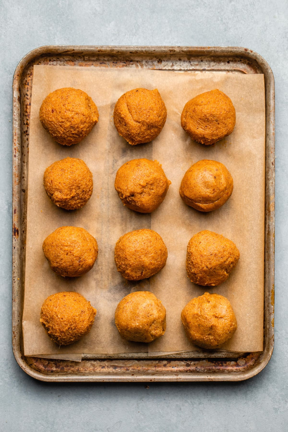 pumpkin truffles rolled into balls on small baking tray lined with parchment paper