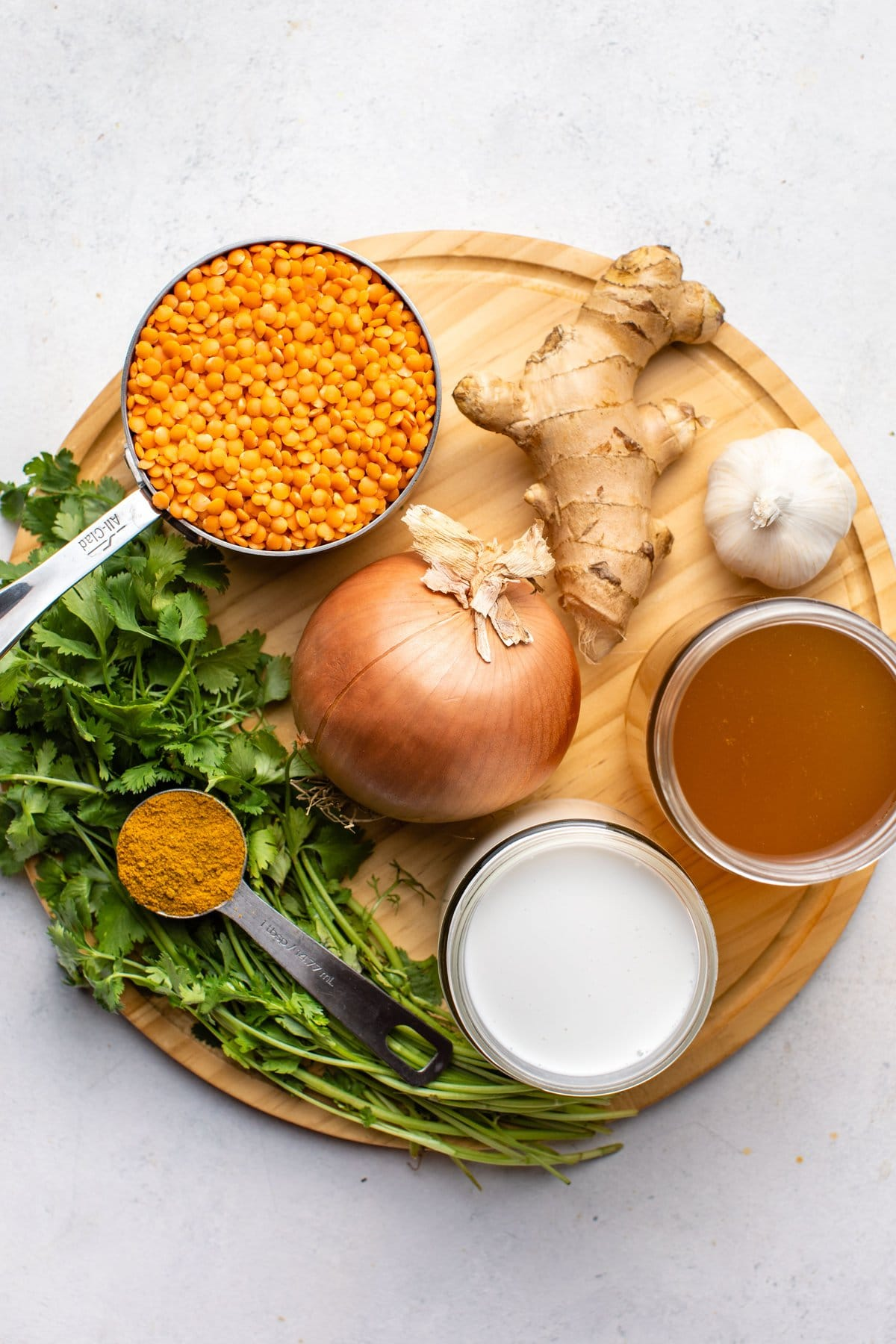 ingredients for coconut red lentil curry on round wood cutting board