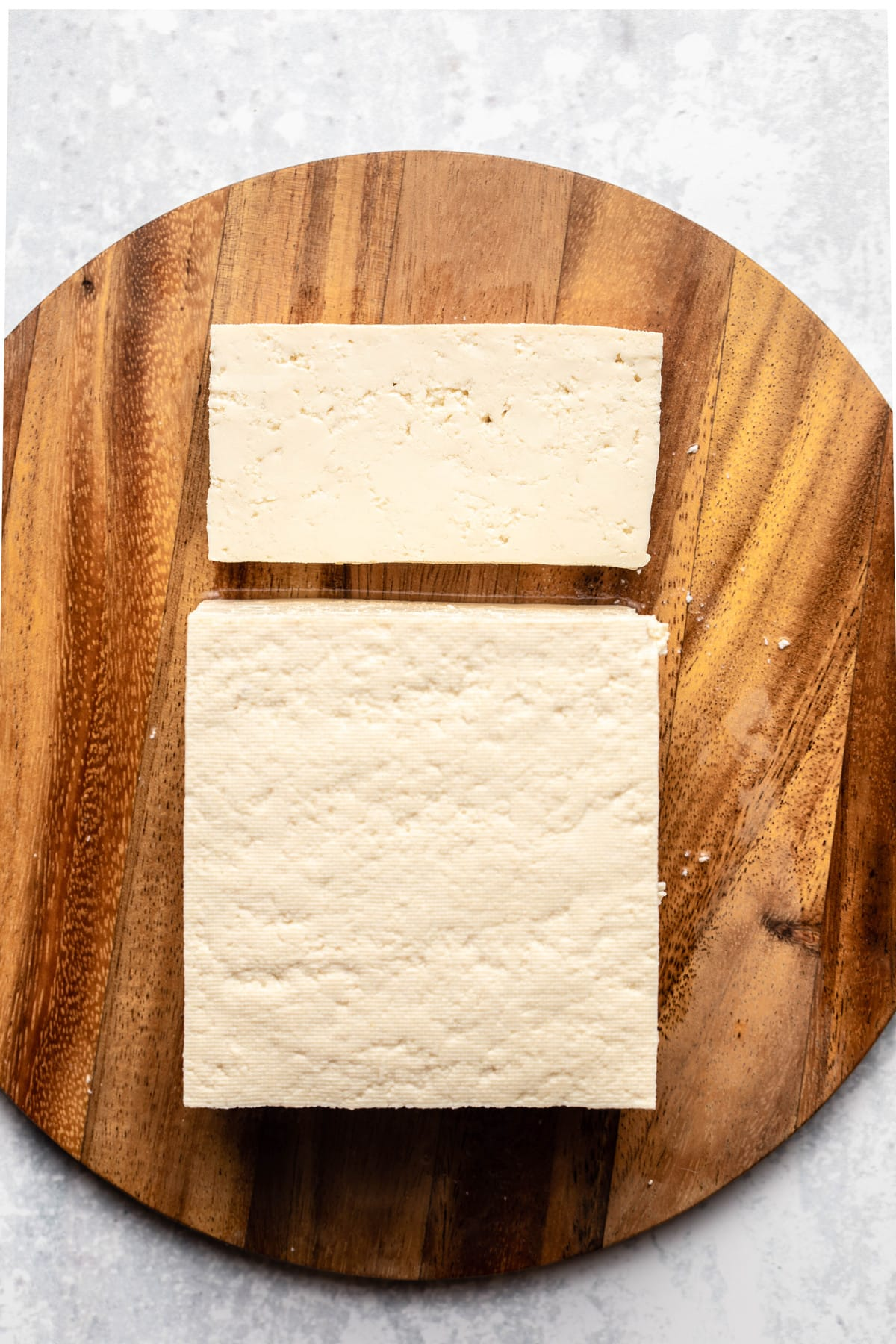 block of extra firm tofu on round cutting board