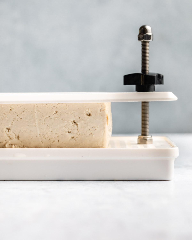 tofu being pressed in a tofu press