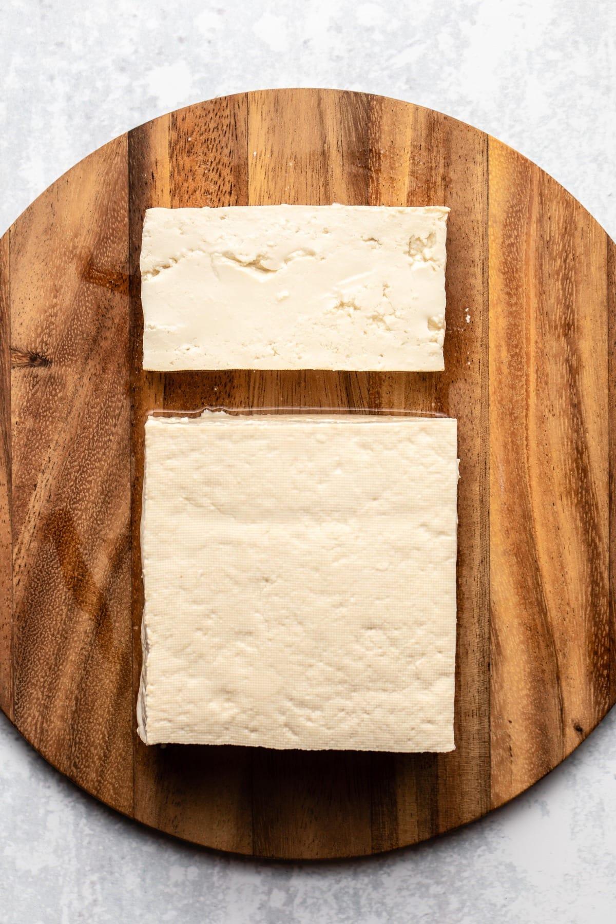 block of firm tofu on round wood cutting board
